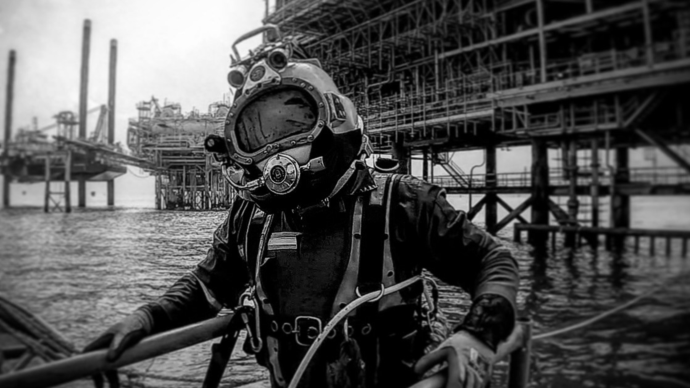 Divers Suited up in the sea near oil platforms